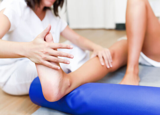 Female physiotherapist inspecting her patient. Medical check at the legs in a physiotherapy center.