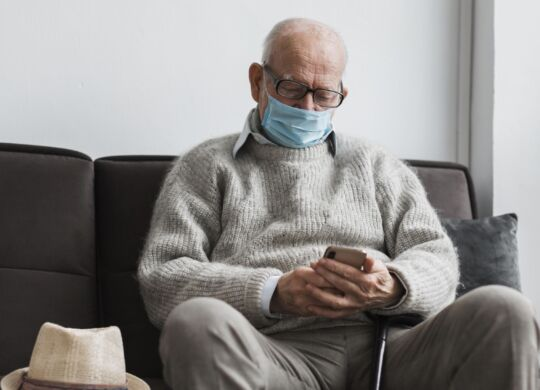 old-man-with-medical-mask-in-a-nursing-home-using-smartphone